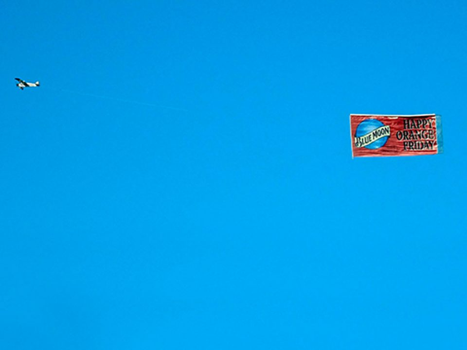 Airplane pulling an advertising flight banner across a blue sky