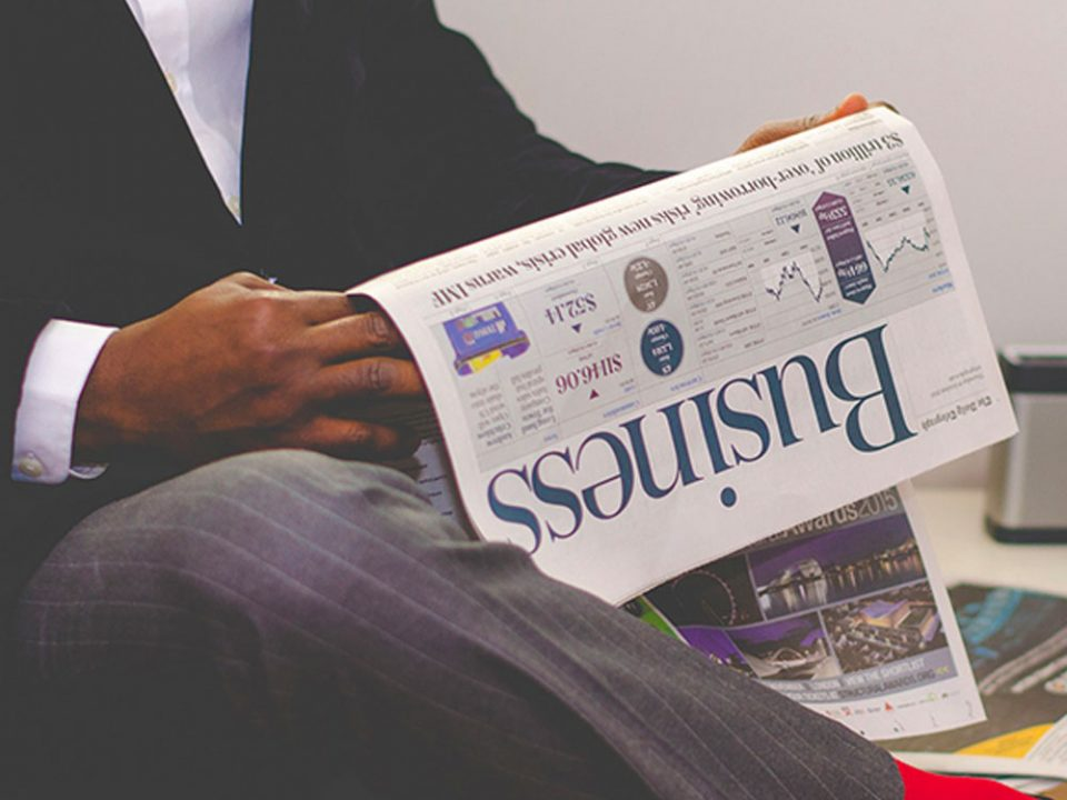 A business man reads the business section of a newspaper