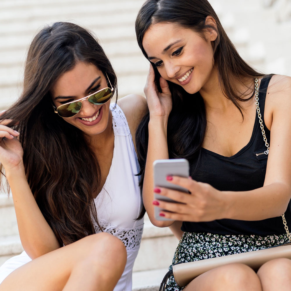 Two women looking at a cell phone