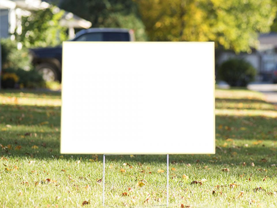 A blank yard sign posted on a lawn.